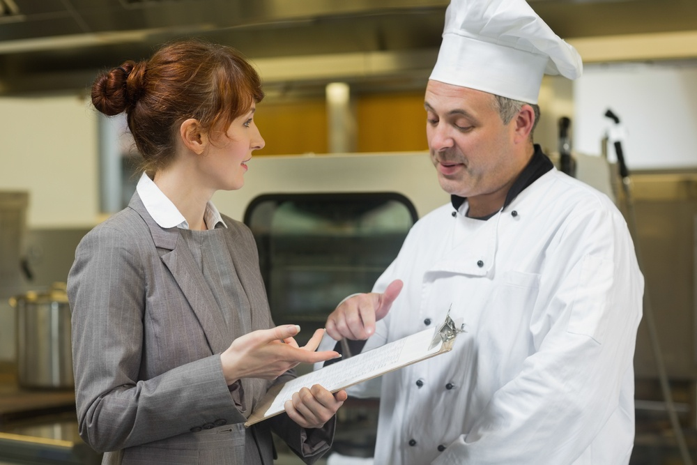 Young female manager talking to the head cook standing in a professional kitchen.jpeg